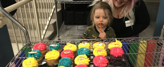 Child and Mother looking at some cupcakes